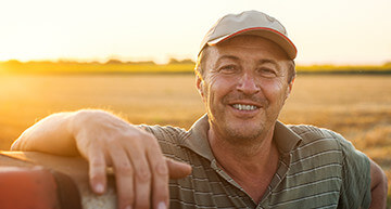 Farmer leaning against a fence at sunset - Farm Insurance