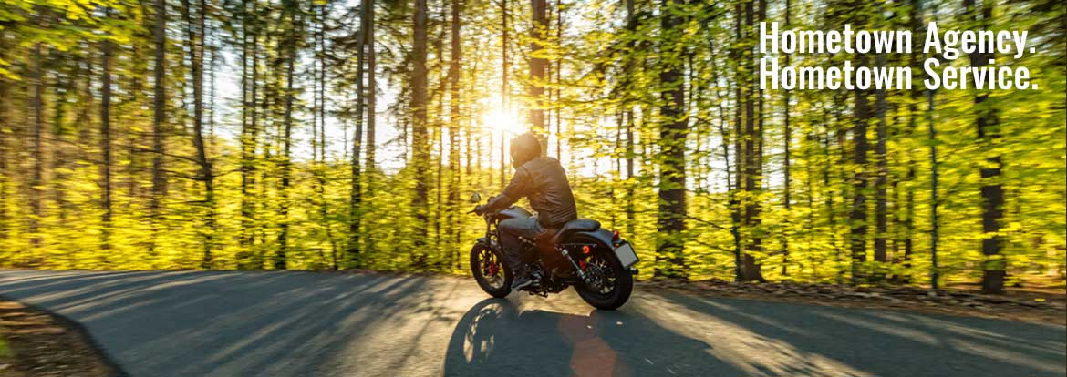 Motorcycle going around a curve at sunset - Motorcycle Insurance