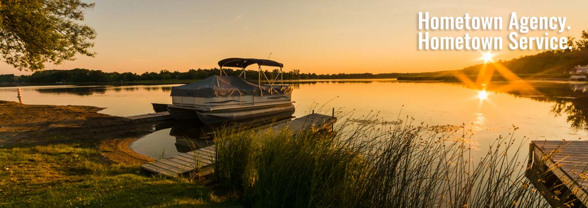Pontoon docked on a lake at sunset - Boat & Recreational Vehicle Insurance